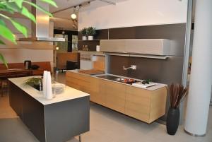 Diese Luxusküche vereint Luxus und kompakte Bauweise. Aufgebaut in zwei Teile bietet diese Ausstellungsküche genügend Platz für die tägliche Arbeit in der Küche und ist dennoch so kompakt, dass Sie auch in kleinere Wohnungen passt.<br />Die modulare Kochinsel besteht dabei aus einer sehr dünnen Arbeitsplatte und dunklen Küchenmöbeln. Komplettiert wird das Ensemble durch eine freihängende Dunstabzugshaube.<br />Die Fronten der Wandzeile sind hingegen in einem hellen Holzton gehalten, der sehr schön mit der beinahe weißen Arbeitsplatte harmoniert. Die Oberschränke sind farblich auf die Küchenmöbel abgestimmt.